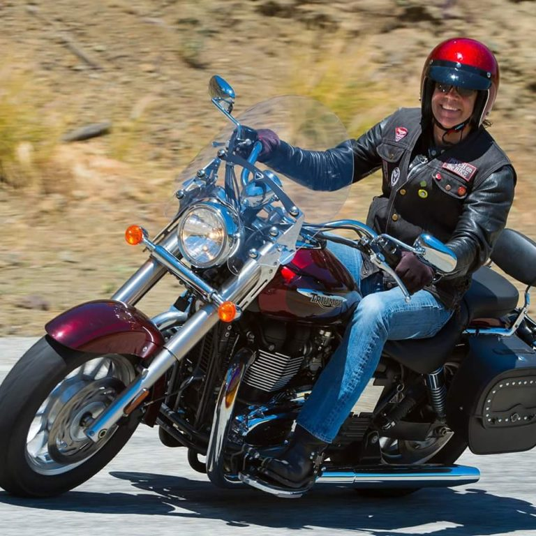 Dr. Stephen Trudeau Riding his red motorcycle through the mountains with a smile on his face - thrive